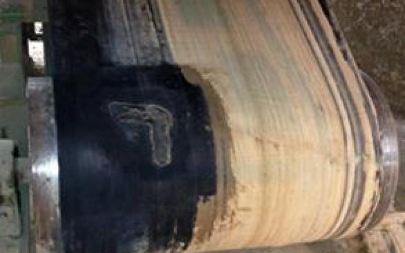 Torn conveyor belt prior to repair